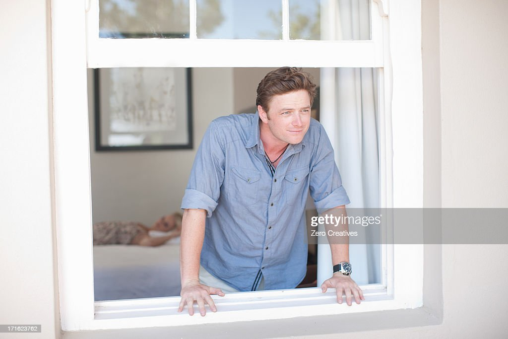 Young man looking through window : Stock Photo