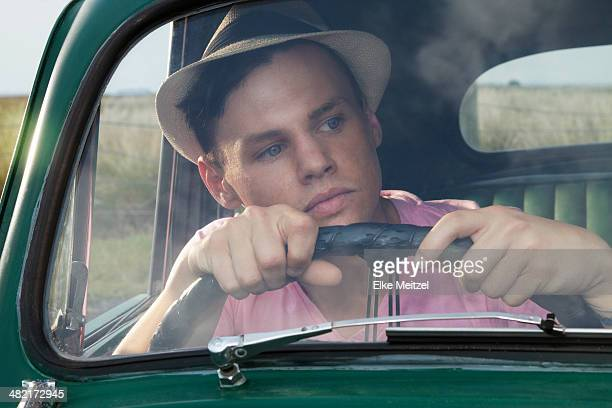 Young man looking through windscreen of vintage morris minor