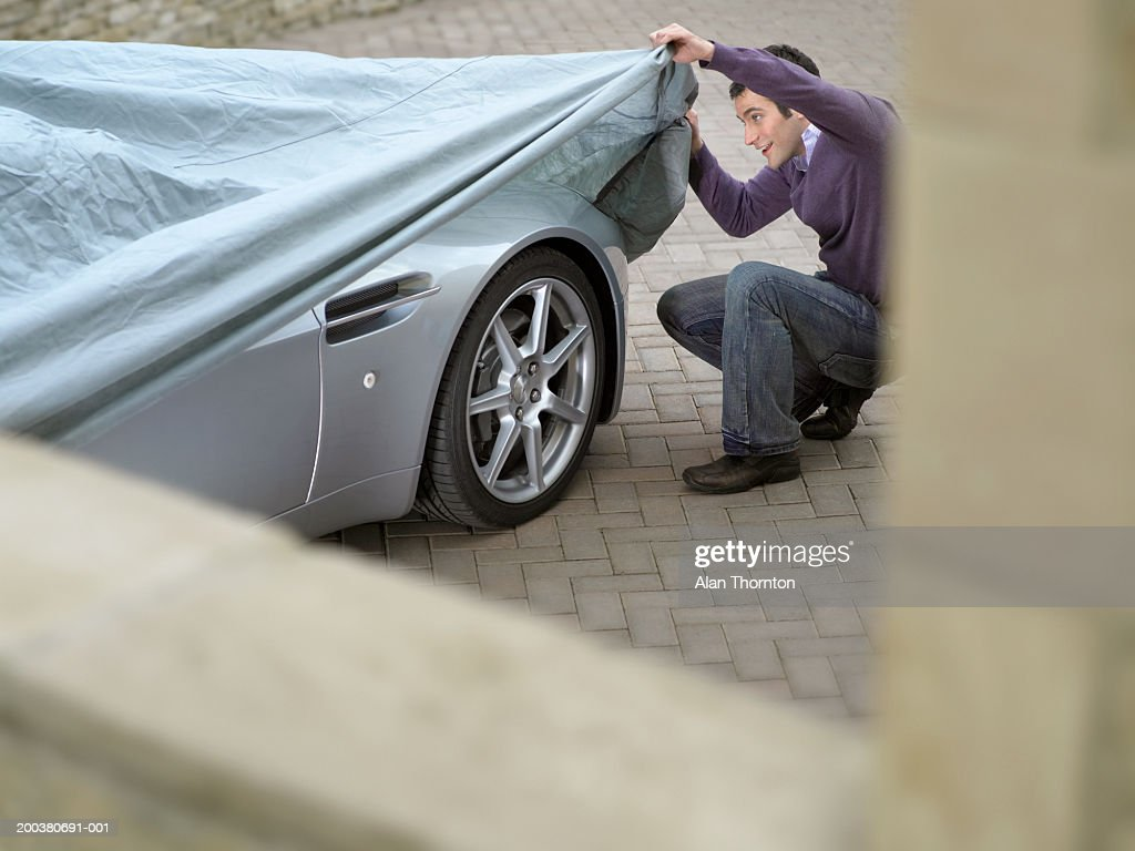 Young man looking under protective sheet on car, smiling : Stock Photo