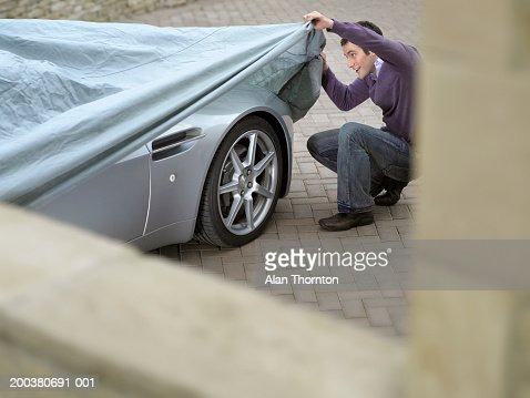 Young man looking under protective sheet on car, smiling : Stock-Foto