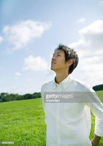 Young man looking up blue sky