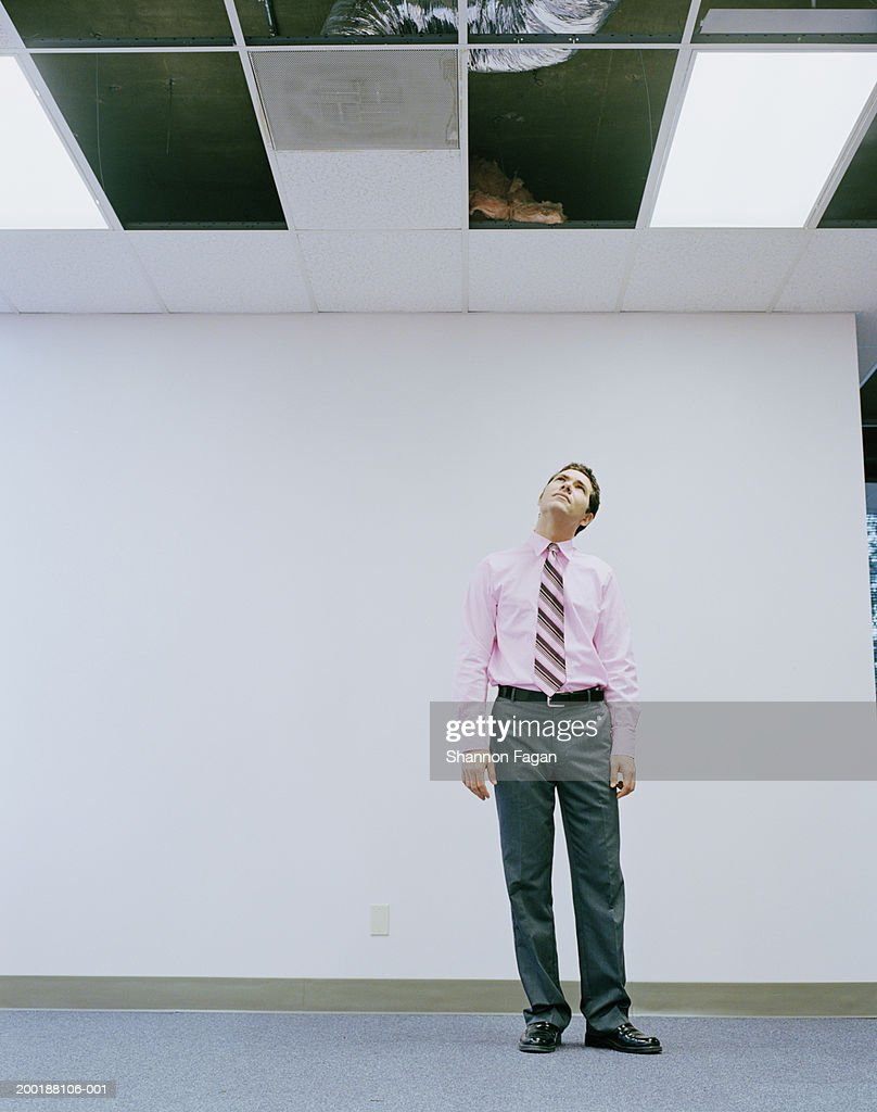 Young man looking up through ceiling panel in office : Stock Photo