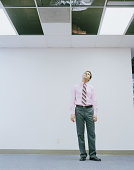 Young man looking up through ceiling panel in office