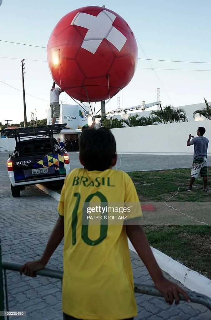 A young man looks at a man pumping up a huge ballon bearing the colours of the Swiss flag during a training session of Switzerland's national football team in Porto Seguro, Brazil, on June 7, 2014, a few days before the start of the 2014 FIFA World Cup .