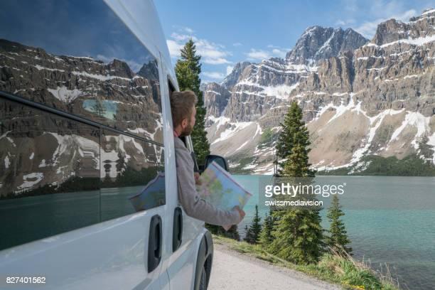 Jeune homme ressemble à la feuille de route près de lac de montagne