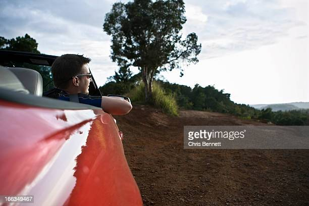 A young man looks out from the passenger seat of a red convertible sports car in Hawaii.