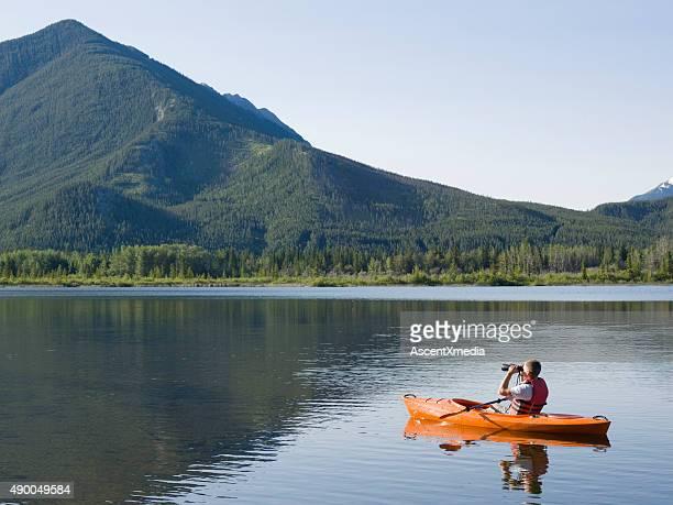 Young man looks through binoculars while kayaking