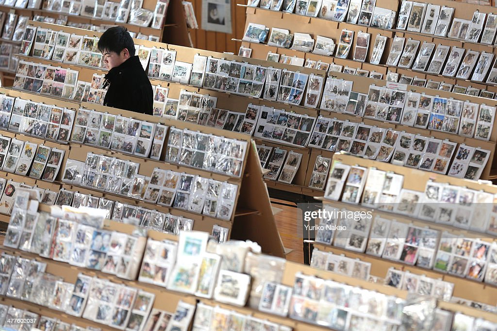 A young man looks through photographs, which were repaired after being washed away by the earthquake and tsunami at a gymnasium March 10, 2014 in Sendai, Miyagi prefecture, Japan. On March 11 Japan commemorates the third anniversary of the magnitude 9.0 earthquake and tsunami that claimed more than 18,000 lives, and subsequent nuclear disaster at the Fukushima Daiichi Nuclear Power Plant.