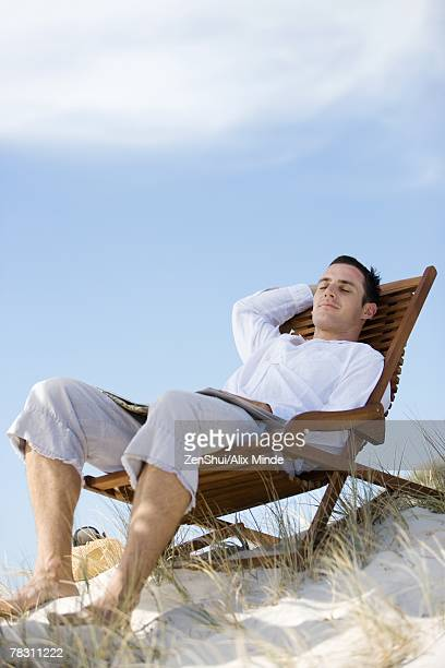Young man lounging in deckchair, eyes closed