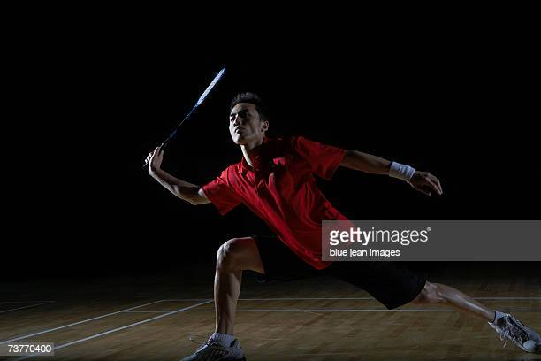 Young man lunges to his right and swings his racket to return a shot during a game of badminton.