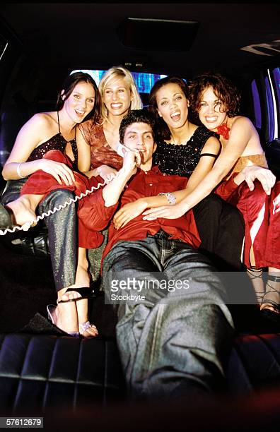 Young man lying in a limousine talking on telephone with a group of young women around him