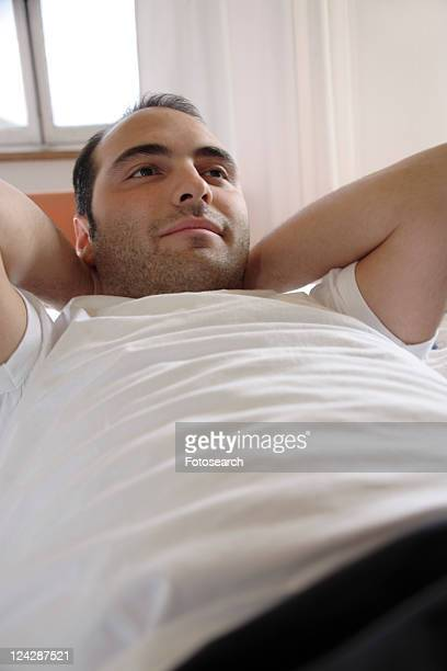 Young man lying in bed, relaxing