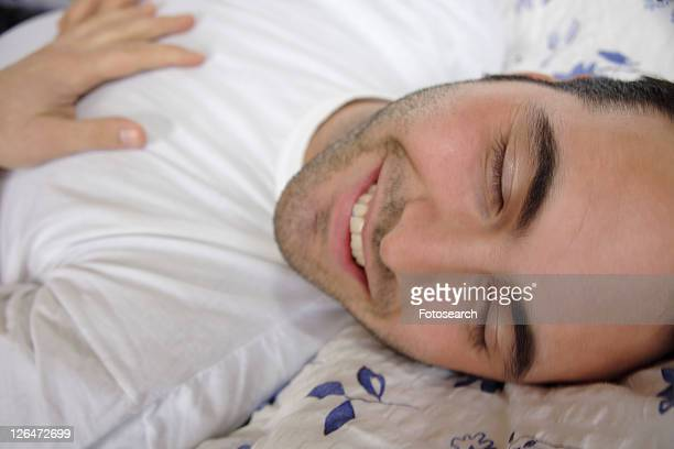 Young man lying in bed, smiling and relaxing