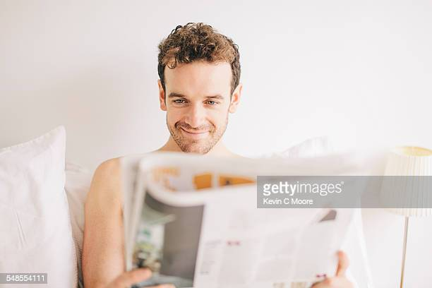 Young man lying in bed smirking whilst reading newspaper