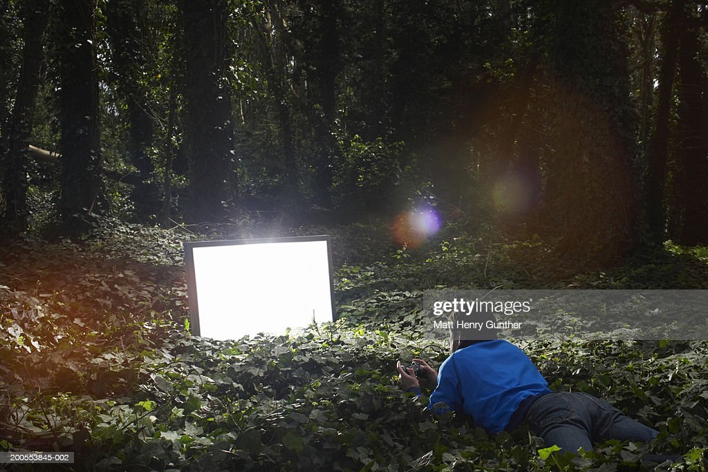 Young man lying in forest, watching lit monitor