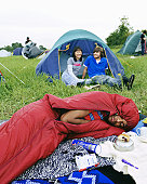 Young man lying in sleeping bag, couple by tent in background