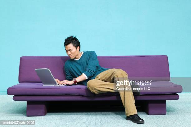 Young man lying on a couch operating a laptop