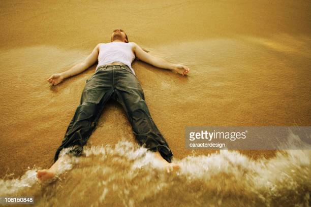 Young Man Lying on Beach and Letting Waves Hit Him