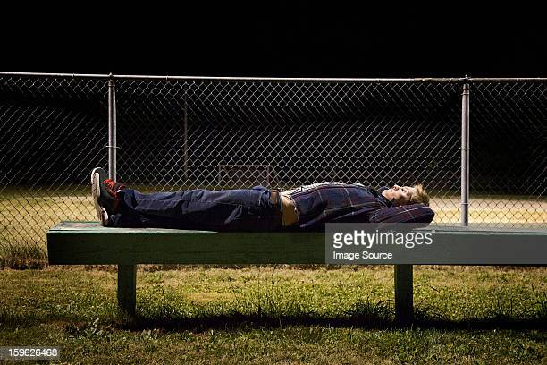 Young man lying on bleachers at night