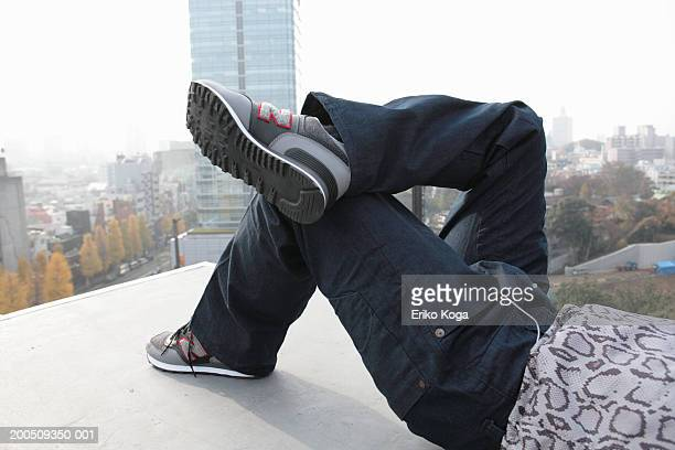 Young man lying on edge of building, low section