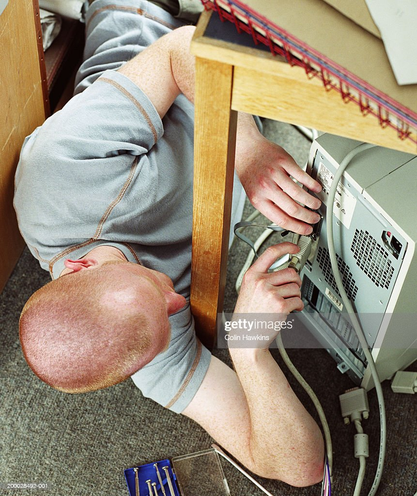 Young man lying on floor connecting computer cable to hard drive : Stock Photo