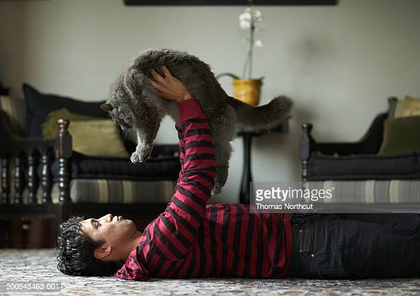 Young man lying on floor, lifting cat up in air, side view