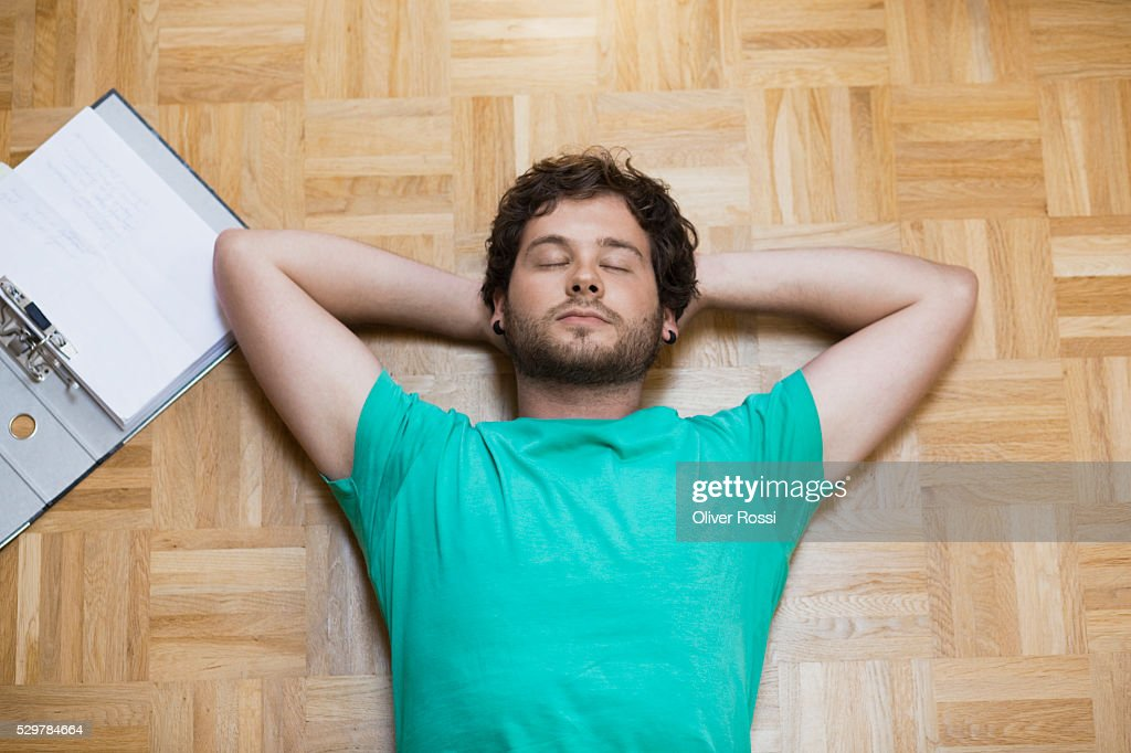 Young man lying on floor next to homework : Stock-Foto