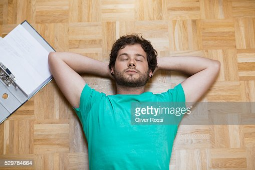 Young man lying on floor next to homework : Stock Photo