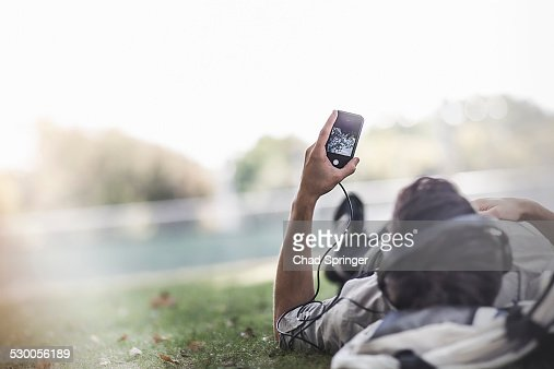 Young man lying on grass in park selecting music on smartphone