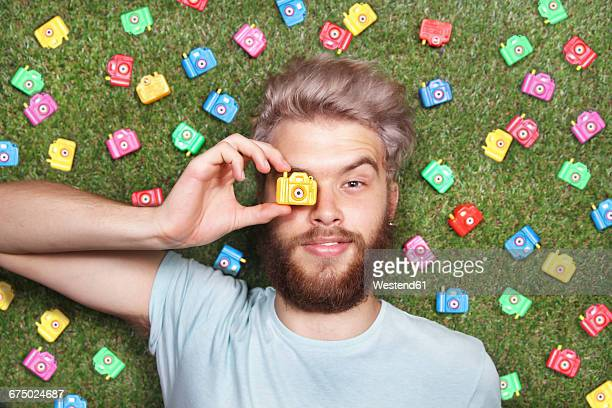 Young man lying on green grass with toy cameras