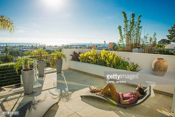 Young man lying on lounger in penthouse rooftop garden, La Jolla, California, USA