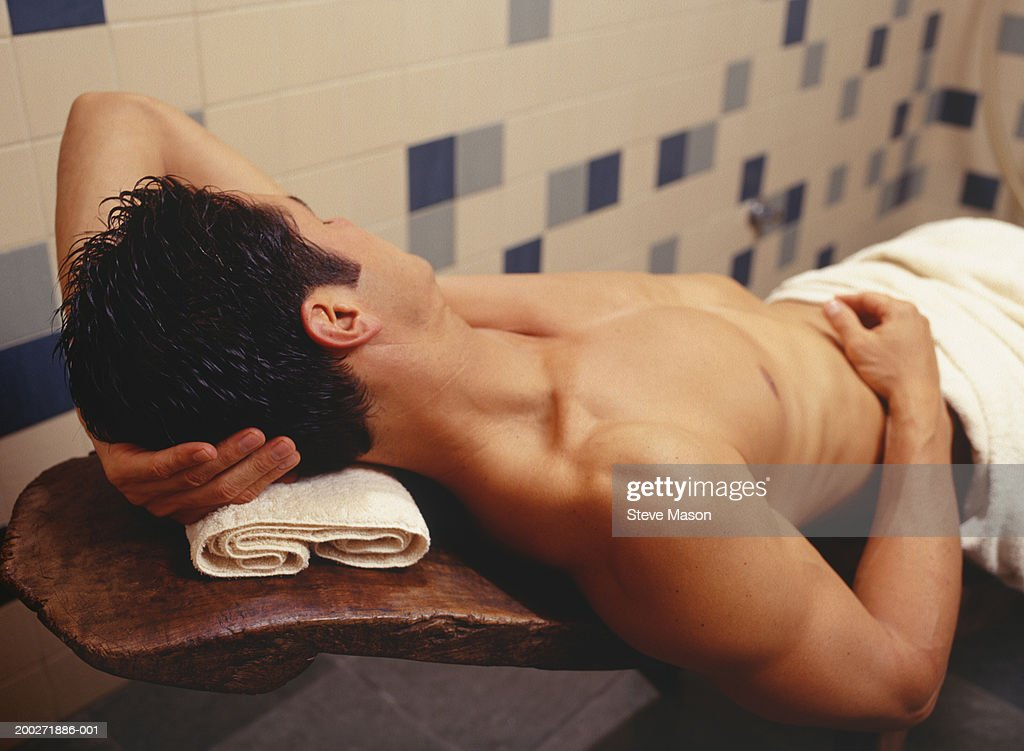 Young man lying on massage table, elevated view : Stock Photo
