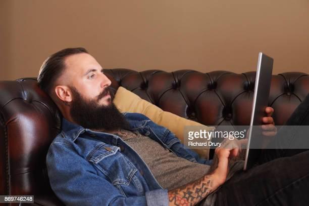 Young man lying on sofa using digital tablet