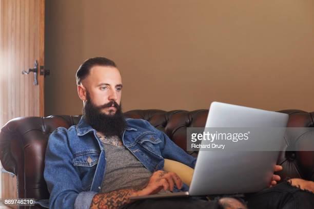 Young man lying on sofa using laptop