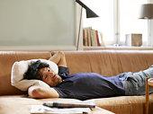 Young man lying on sofa watching TV