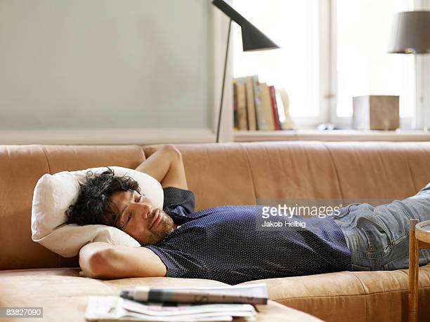 Young man lying on sofa watching TV