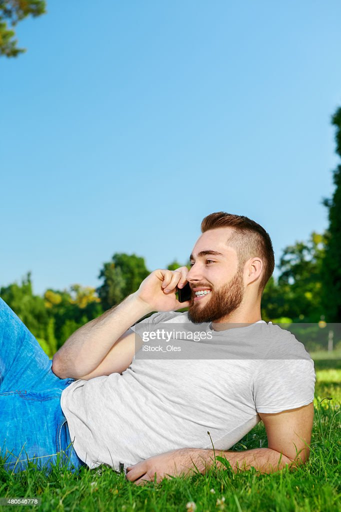 Young man lying on the grass en un parque con teléfono : Foto de stock