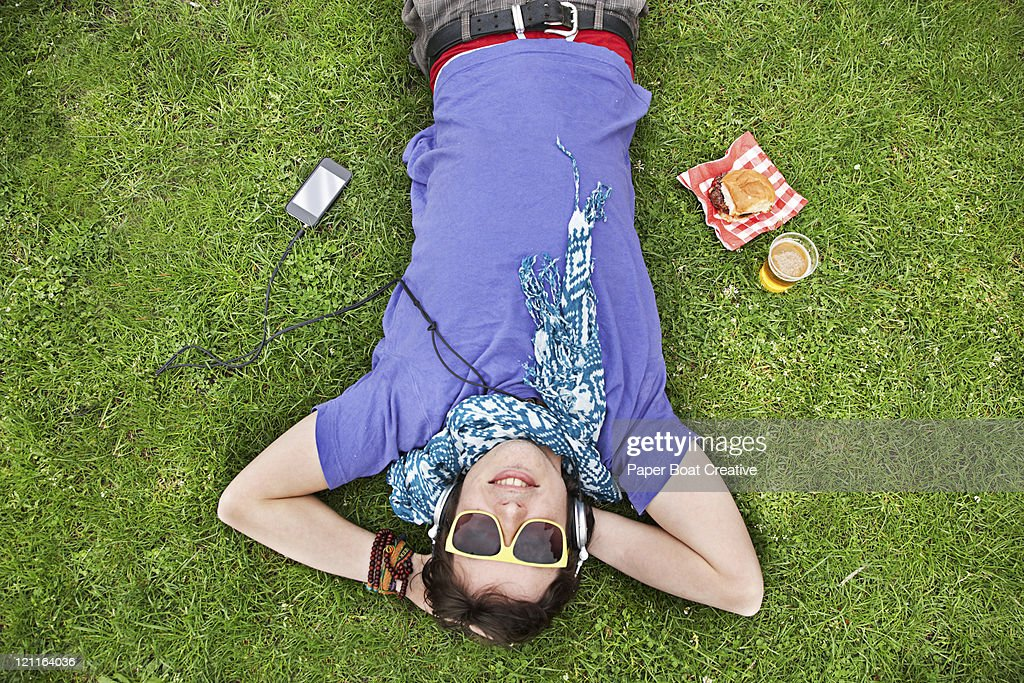 A young man lying on the grass with beer and food : Stock Photo
