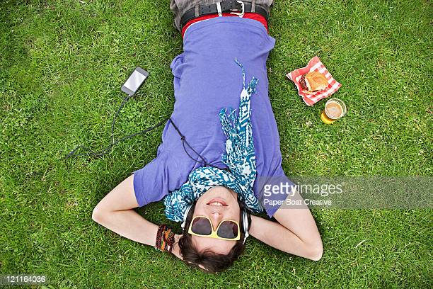A young man lying on the grass with beer and food