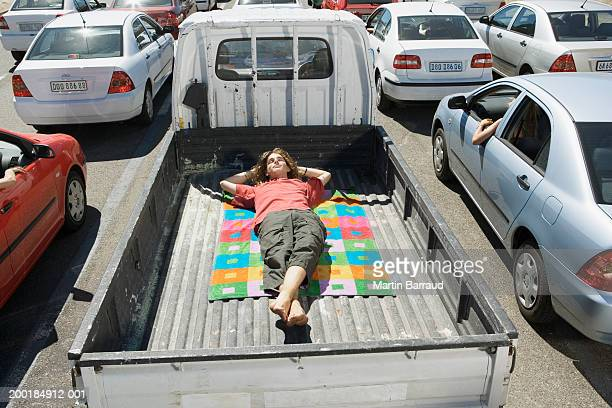 Young man lying on towel in back of pickup truck amongst traffic jam
