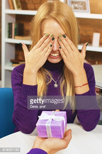 Young man makes gift to a girl who closes her : Stock Photo