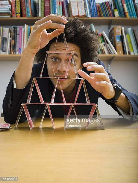Young man making a house of cards