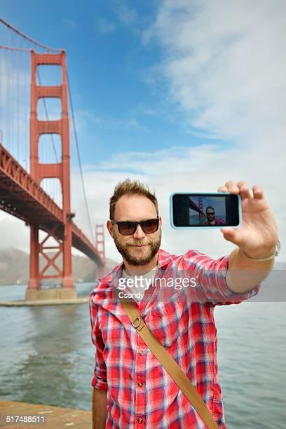 Jeune homme faisant un selfie avec le Golden Gate