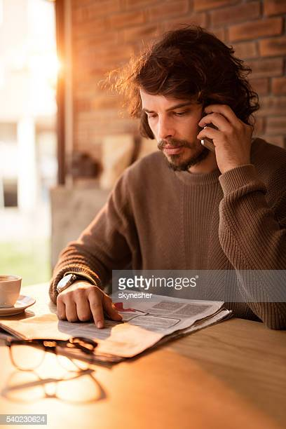Young man making appointment for job interview over cell phone.