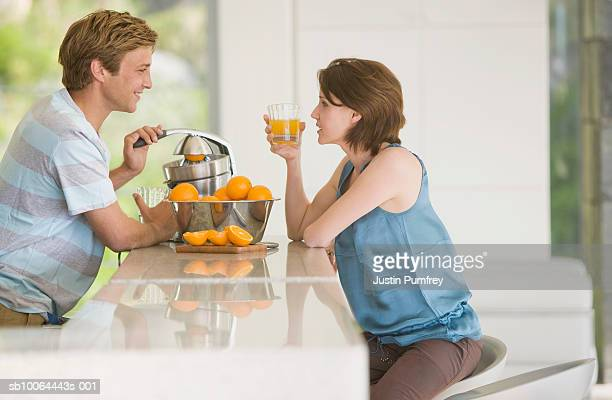 Young man making fresh orange juice for woman, side view