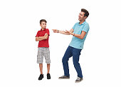Young man making fun of his little brother over a white background. Horizontal composition. Studio shot.
