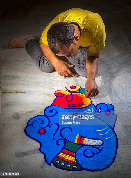 Young man making Rangoli on the occasion of Diwali