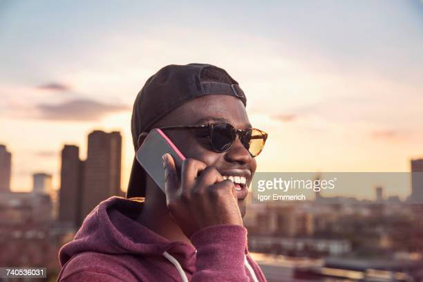 Young man making smartphone call at sunset roof party in London, UK