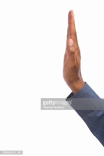 Young man making stop gesture, side view, close-up of hand