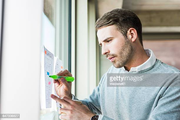 Young man marking papers at the window
